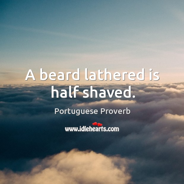 A beard lathered is half shaved. Image