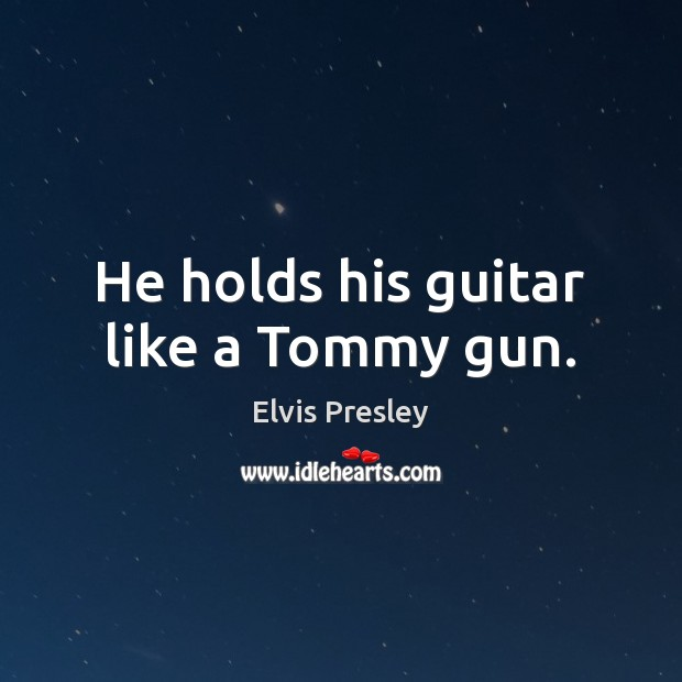 He holds his guitar like a Tommy gun. Image