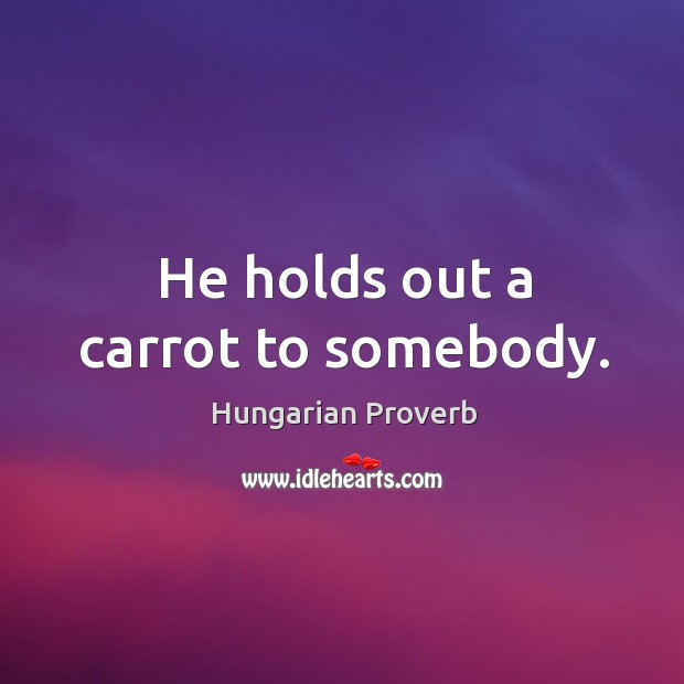 He holds out a carrot to somebody. Image