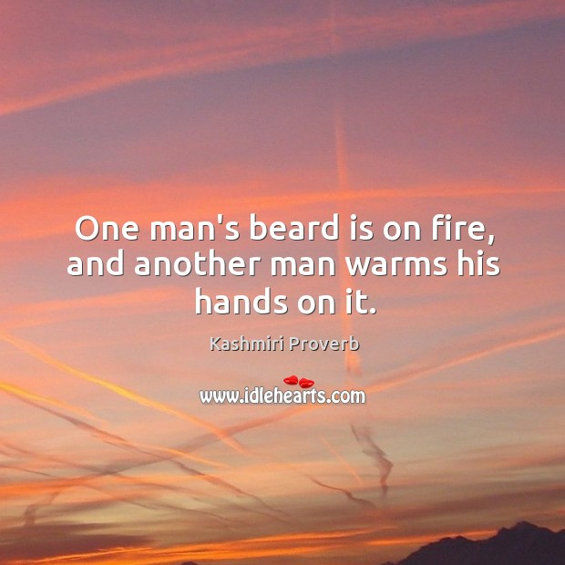 Image, One man's beard is on fire, and another man warms his hands on it.
