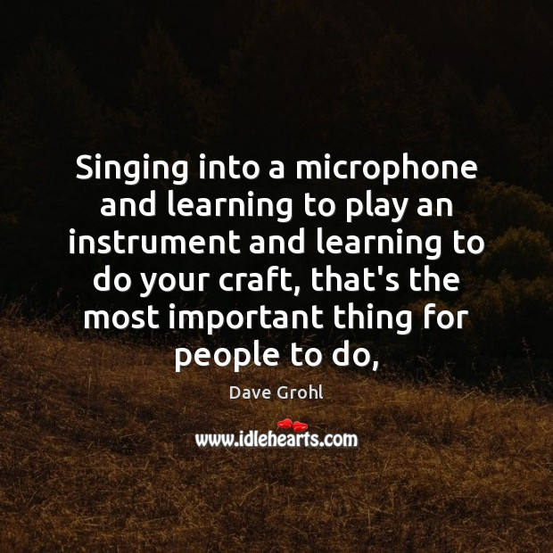 Singing into a microphone and learning to play an instrument and learning Image