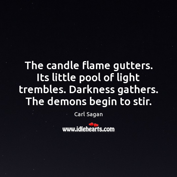 The candle flame gutters. Its little pool of light trembles. Darkness gathers. Image
